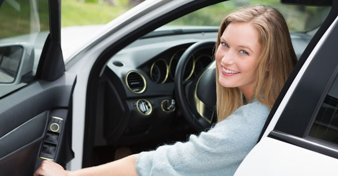 A young woman in the driver's seat of her car