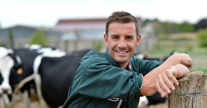 A farmer leaning against a fence